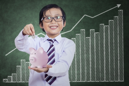 Little boy puts the coin into the piggy bank at classroom photo