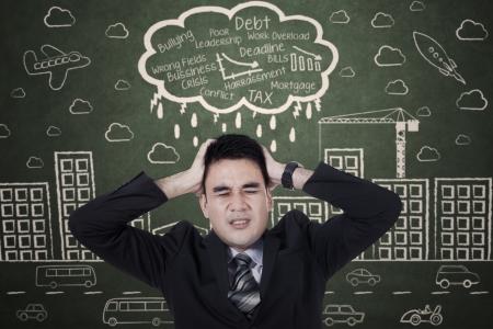 financial crisis: Stressed asan businessman with a headache on chalkboard Stock Photo