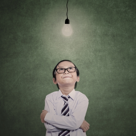 child looking up: Little businessman looking at lit bulb in class with blank chalkboard Stock Photo