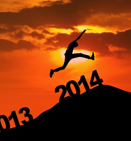 january sunrise: Man jumping over 2014 number to embrace the new year