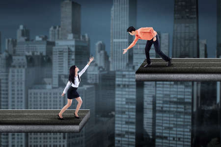 helpful: Asian businessman standing on the bridge and helping businesswoman by hand