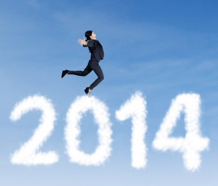 Happy asian businesswoman is jumping over clouds of 2014 photo