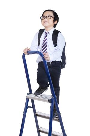 niño escalando: Niño que sube una escalera aislados en fondo blanco Foto de archivo