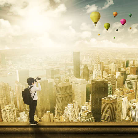 rooftop: Child standing on the top of a skyscraper and looking at hot balloons