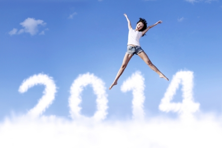 Excited asian woman is jumping with new year 2014 on the sky Stock Photo - 22491588