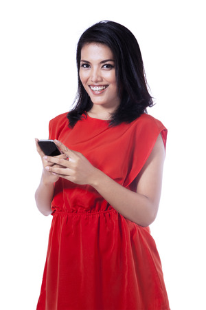Happy young woman touching and browsing her smartphone photo