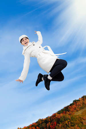 Happy woman jumping in a autumn day photo