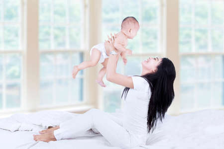 Side view of young asian mom lifting happy baby into air above head photo