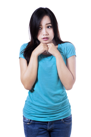 solicitous: Young woman with nervous expression isolated on white background