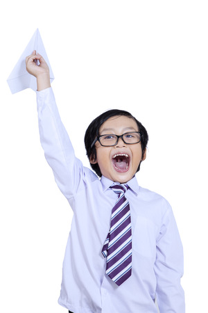 Excited schoolboy holding a paper airplane isolated on white background photo