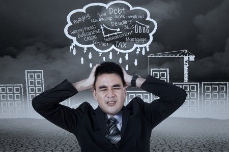 Stressed businessman with a headache under stormy clouds photo