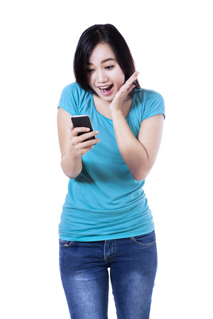 sms: Surprised young woman reading a text message on the mobile phone