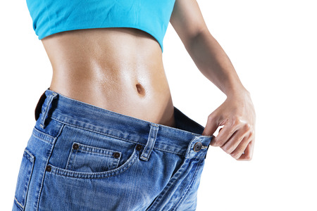 asian abs: Weight loss concept: Slim woman pulling oversized jeans