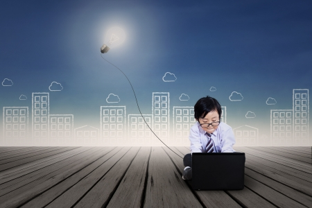 boy with glasses: Asian kid with business clothing working on laptop. Background is scribble of cityscape