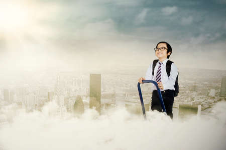 Portrait of an ambitious little businessman on a ladder stepping up Stock Photo - 22632786