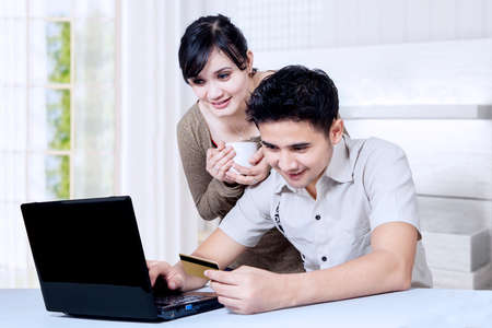 Couple shopping online at home photo