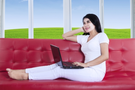 Beautiful young female is working on laptop while sitting on red sofa photo
