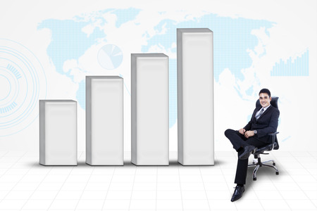 Asian businessman sitting on chair with bar chart on world map background