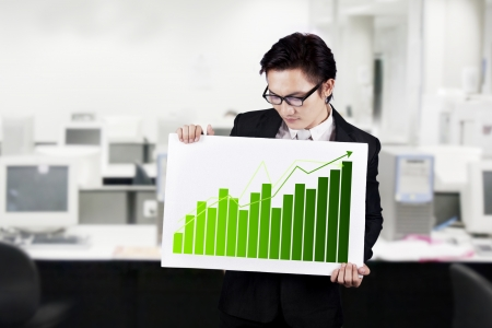 Young businessman showing a business graph board photo