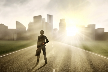 Businesswoman looking for a future and standing on the highway of a skyscraper with cityscape photo