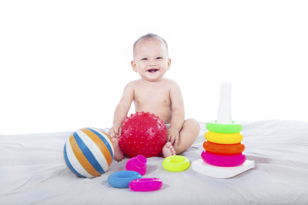 Cute baby with colorful toys on white background photo