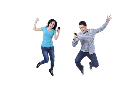 mobile communication: Excited young couple jumping with mobile phone