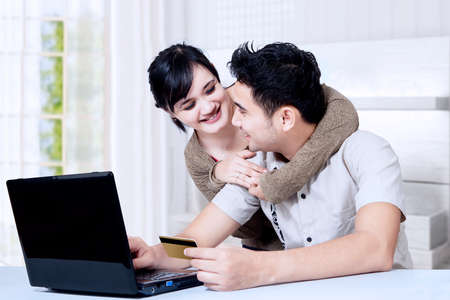 Portait of happy asian couple online shoping at home photo