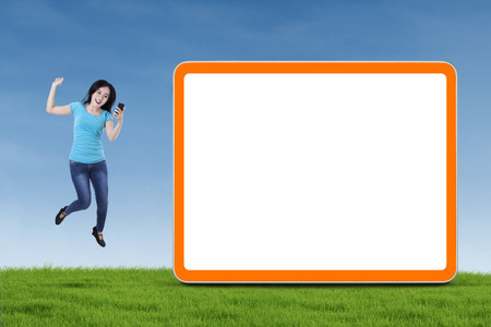 Happy asian girl holding smartphone and jumping next to blank board photo