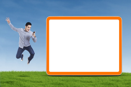 Happy asian man holding smartphone and jumping next to blank board photo