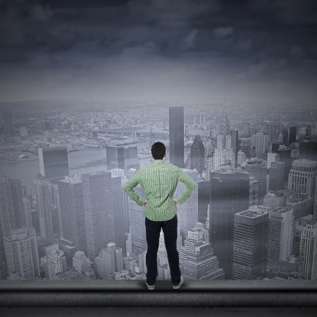 global thinking: Portrait of a young man looking into the future standing on the top of a skyscraper
