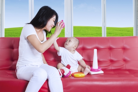 Asian mother and baby playing with toy sitting on red sofa photo
