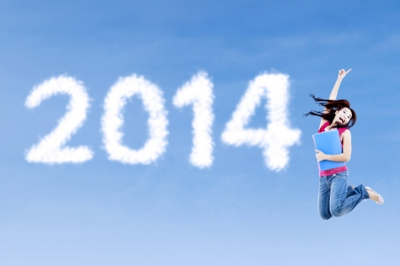 Female college student jumps on the side of number 2014 Stock Photo - 22658363