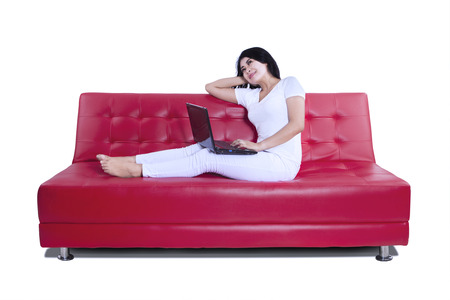 Beautiful woman using laptop on red sofa on white background Stock Photo - 22658384