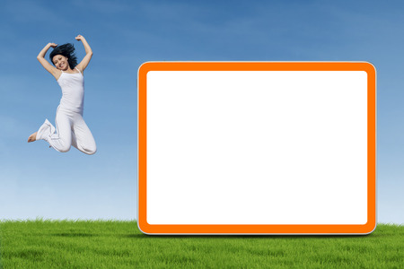 A young fitness woman jumping next to empty board on the green grass  photo