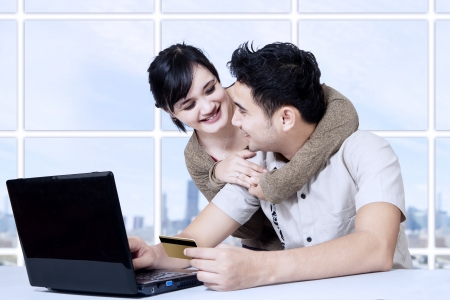 Portrait of happy asian couple online shopping at appartment Stock Photo - 22658511