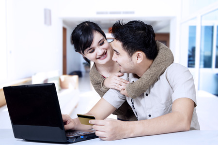 Portrait of happy asian couple online shopping at home photo