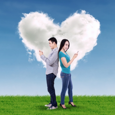 Young couple using mobile phone with heart cloud background photo
