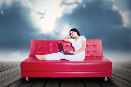 Portrait of beautifull woman using laptop on couch photo