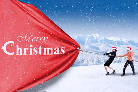 Asian business team pull christmas banner Stock Photo - 22615796