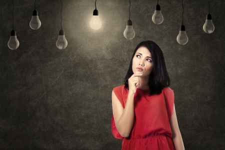 Creative woman looking at bright lightbulb photo