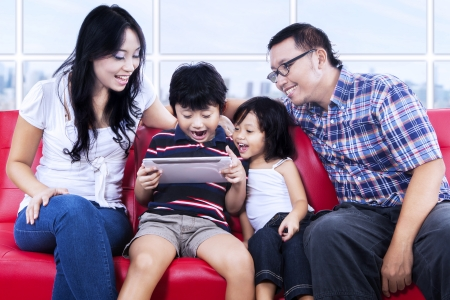 Excited family playing game with e-tablet at apartment i Stock Photo - 22658824