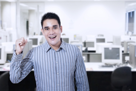 Excited young businessman with arms up at office photo