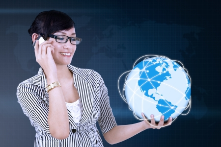 Portrait of young asian woman calling and holding globe photo