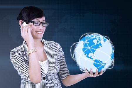 holding globe: Ritratto di giovane donna asiatica chiamata e globo