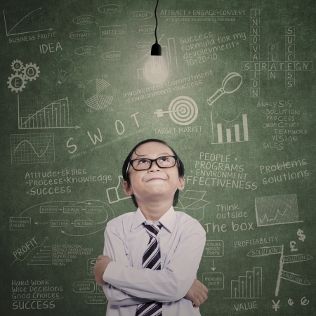 nerd glasses: Little businessman looking at lit bulb with drawn formula on the board