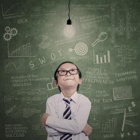 niños pensando: Pequeño hombre de negocios mirando bombilla encendida con la fórmula dibujado en la pizarra Foto de archivo