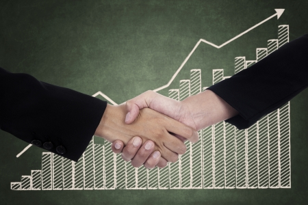 Businessman and businesswoman handshake with growth graph background Stock Photo - 22658834