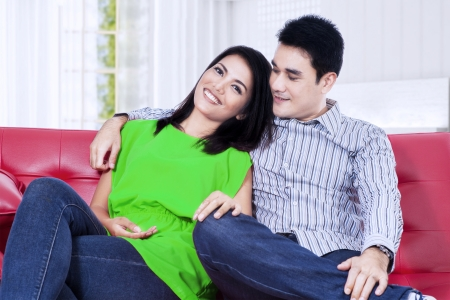 Happy couple relaxing on a red sofa at home photo