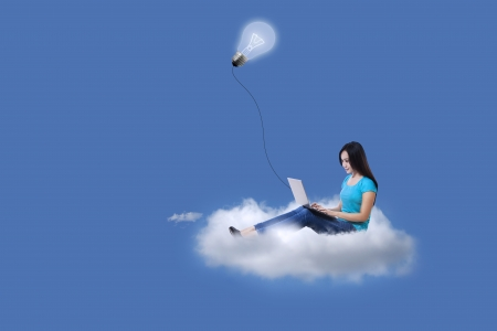 Beautiful woman sitting on cloud using laptop under light bulb Stock Photo - 22663391