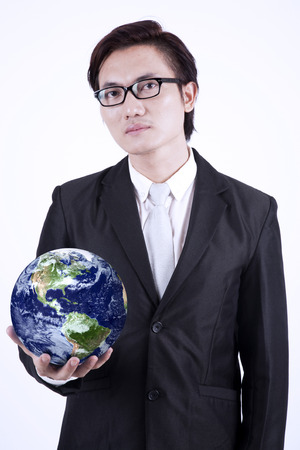 courtesy: Confident asian businessman holding the planet earth isolated over white background. Earth image courtesy NASA